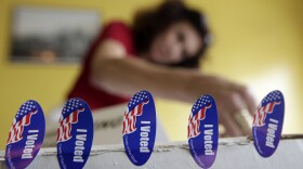 """Poll worker Melanie Withey attaches """"I voted"""" stickers to a box at a polling station on election day in San Diego, June 8, 2010."""
