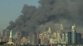 Thick smoke billows into the sky from the area behind the Statue of Liberty, lower left, where the World Trade Center towers stood, on Tuesday, Sept. 11, 2001. The towers collapsed after terrorists crashed two planes into them.