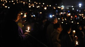 People hold candles during a vigil for shooting victims on Thursday at San Manuel Stadium in San Bernardino, Dec. 3, 2015. A husband and wife opened fire on a holiday banquet, killing multiple people on Wednesday. Hours later, the couple died in a shootout with police.