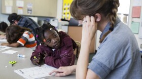 A young girl works with a tutor during a San Diego Refugee Tutoring session at Ibarra Elementary School in City Heights, April 27, 2017.