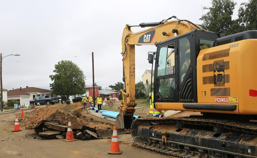 A crew from TC Construction works on replacing cast iron pipes on 60th Street with new PVC pipes, Oct. 16, 2015.