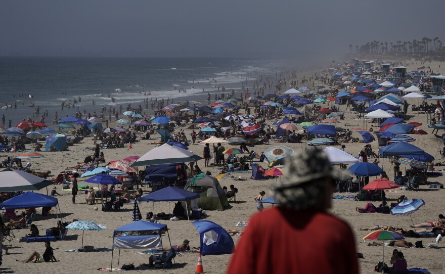 People crowd the beach in Huntington Beach, Calif., over the long Labor Day weekend last year, months before COVID-19 vaccines were available. This year, the CDC is recommending that people who are not fully vaccinated stay home.