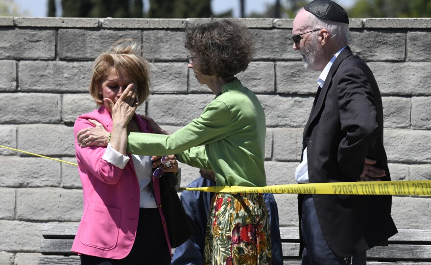 Synagogue members console one another outside of the Chabad of Poway Synagogue Saturday, April 27, 2019, in Poway, Calif. Several people were injured in a shooting at the synagogue.