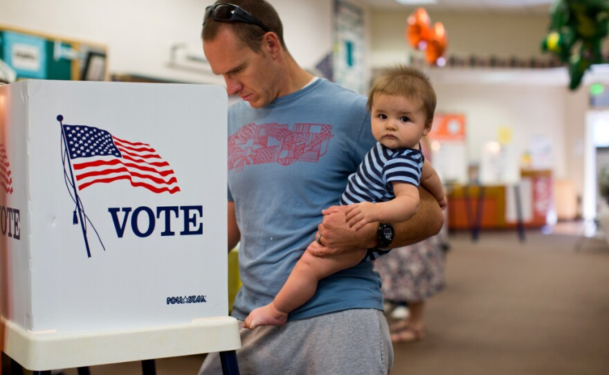 Jeff Thompson holds his 8-month-old son, Tyler, while voting in the Los Angeles County primary election at Canyon Springs School's library on in Santa Clarita, June 3, 2016.