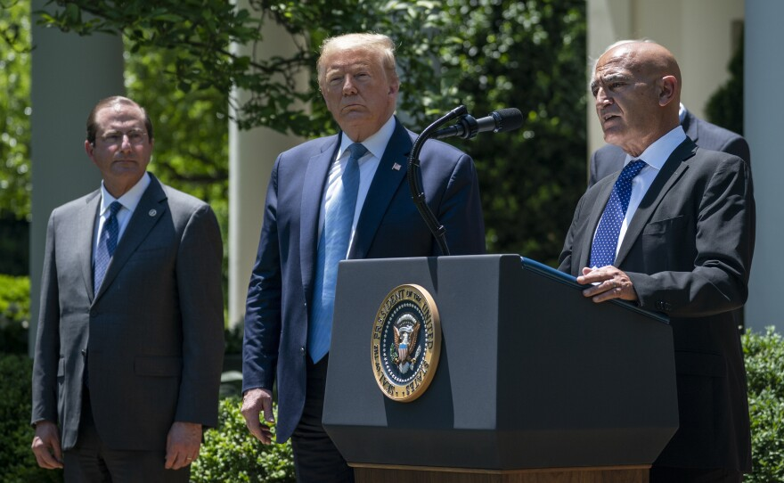 Then-Health and Human Services Secretary Alex Azar (left) and President Donald Trump listen as Moncef Slaoui of Operation Warp Speed speaks about the crash program to develop a COVID-19 vaccine in the White House Rose Garden on May 15, 2020.