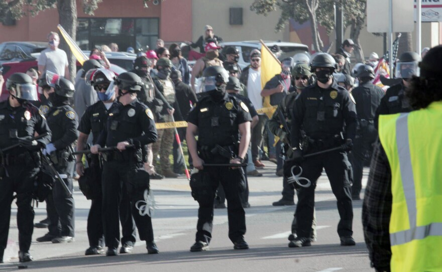 San Diego police officers forming a chain separating pro-Trump supporters and counter-protesters in Pacific Beach on Jan. 9, 2021.