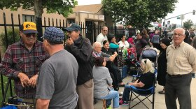 Nearly 250 people line up in front of the Salvation Army in El Cajon to receive groceries during a Jacobs & Cushman Food Bank distribution event, May 15, 2019.