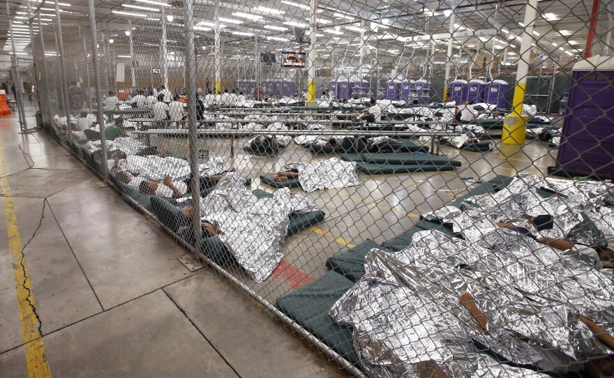 Detainees sleep and watch television in a holding cell where hundreds of mostly Central American immigrant children are being processed at a U.S. Customs facility in Nogales, Texas.