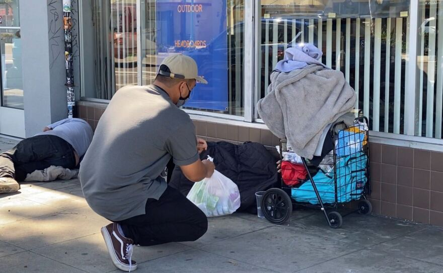 Jessie Angeles Jr. delivers a bag of food to one of his homeless clients, May 28, 2020.