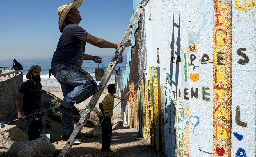 From left, Luis Marmolejo, Enrique Chiu and Sergio Tellez, begin painting sections of fencing along the U.S.-Mexico border at Friendship Park in Tijuana on Oct. 7, 2017. Chiu, a muralist, has worked for nearly a year to paint messages of hope in what could become the world's largest mural.