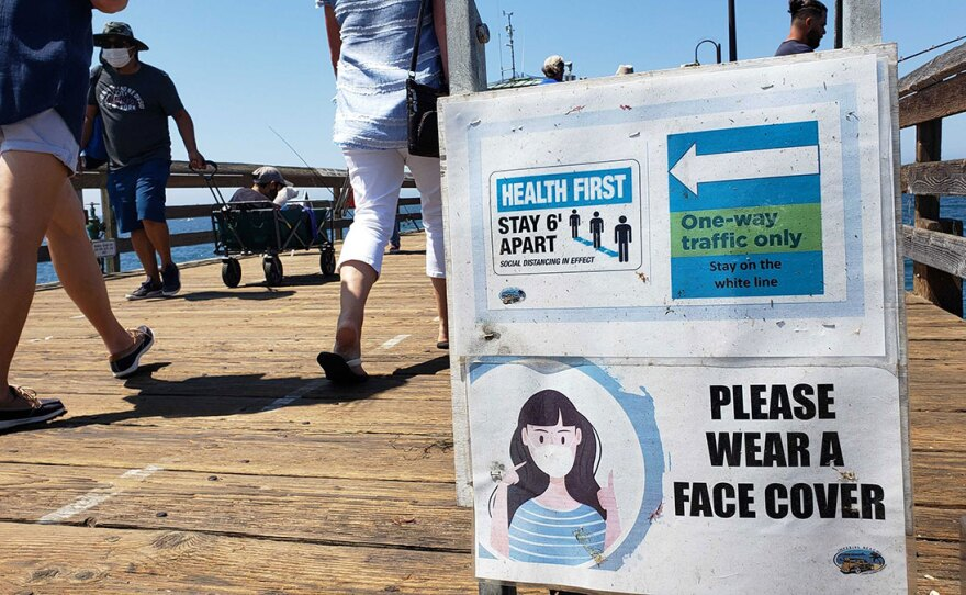 A sign warns people to practice social distancing and to wear a mask at the Imperial Beach pier, Sept. 14, 2020.