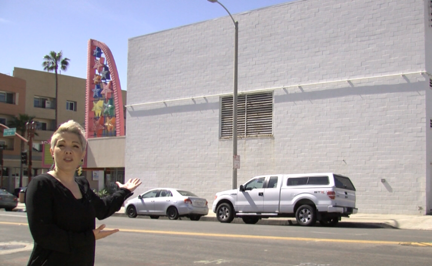 Mitzi Summers points to a large white wall on the side of the Star Theatre that will be the location of the first winning muralist in the Oceanside murals initiative, March 28, 2017.
