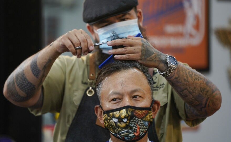 In this May 27, 2020 file photo Luis Lopez wears a face mask while giving a hair cut to Alexander Chin at Orange County Barbers Parlor in Huntington Beach, Calif.