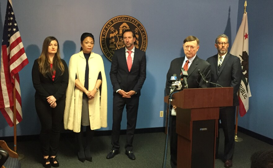 San Diego City Attorney Jan Goldsmith stands at a podium, while Benelia Santos-Hunter, second from the left, stands in the background, at a press conference announcing a settlement in Santos-Hunter's case against former San Diego Mayor Bob Filner, Feb. 2, 2016.
