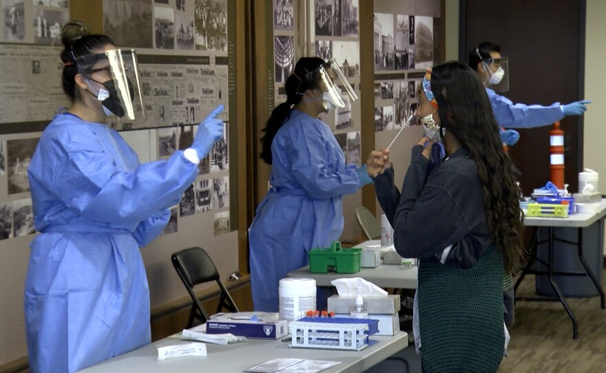 Mission Valley resident Riannah Bisco (left) gets ready to take a coronavirus test at the San Diego State Alumni Center, August 6, 2021.