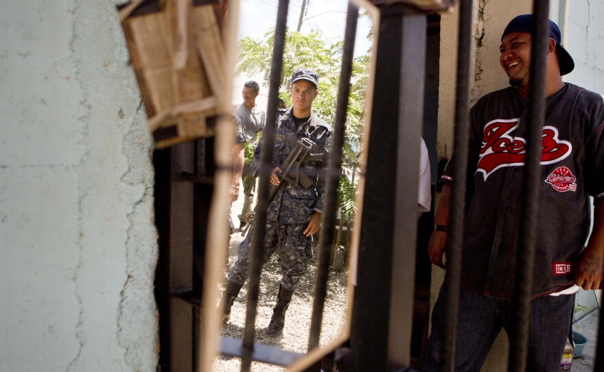 A national police officer is reflected in a mirror hanging inside the area of gang members from the Mara Salvatrucha, or MS, inside the San Pedro Sula prison in Honduras, May 28, 2013.
