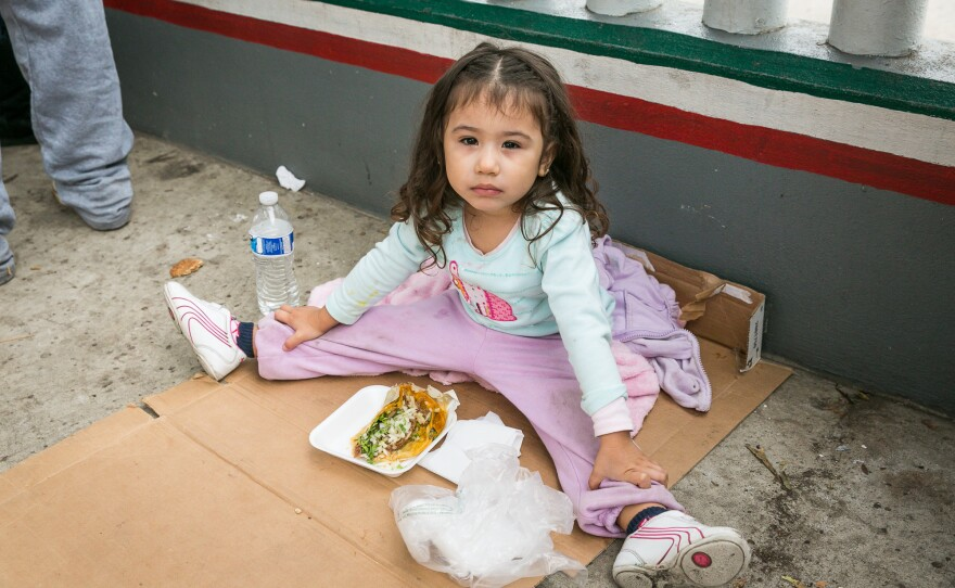 The three-year-old daughter of Blanca Campozano and Edgar Valencia, who along with their infant son are seeking asylum in the U.S., waits to cross the border in Tijuana, Oct. 25, 2018.