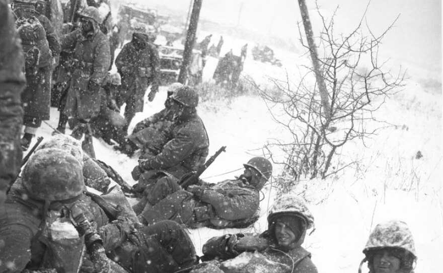Men of a U.S. Marine mortar squad rest at the side of a snowy road during their withdrawal from the Chosin Reservoir, North Korea. Dec. 8, 1950.