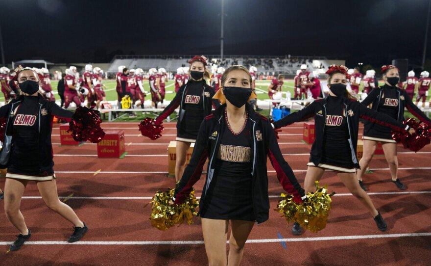 El Modena High School cheerleaders perform during the school's football game with El Dorado High School in Orange, Calif., Friday, March 19, 2021.