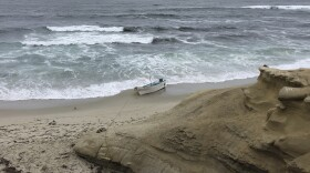A small boat used during a suspected human smuggling operation sits on La Jolla beach in San Diego, on Thursday, May 20, 2021. Authorities said multiple people believed to have been aboard the boat were rescued from the ocean along the San Diego coast early Thursday.
