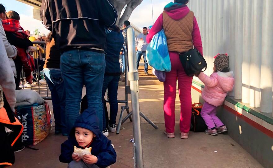 People seeking asylum in the United States wait at the border crossing bridge in Tijuana, Mexico, Wednesday, Jan. 8, 2020.
