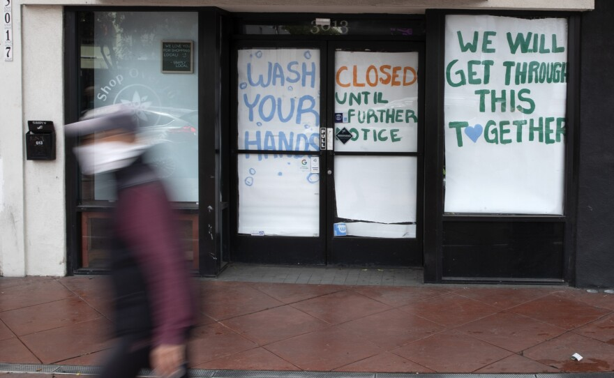 A man passes a store that closed as part of efforts to combat the spread of the new coronavirus Thursday, April 9, 2020, in San Diego.