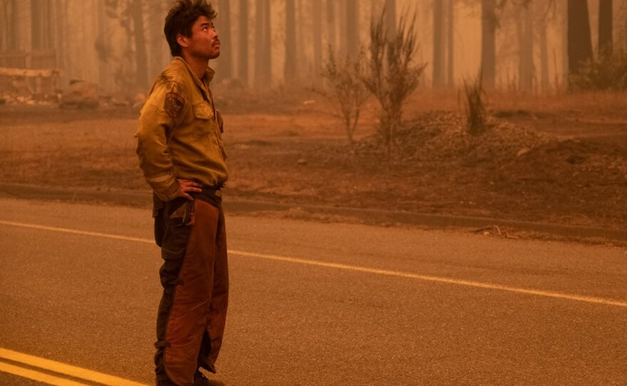Megalia Calif. based CalFire firefighter, Itto Akiyama, rests briefly after 48 hours of work at the Bear Fire near Oroville, Calif. Wednesday., Sept 9. 2020.