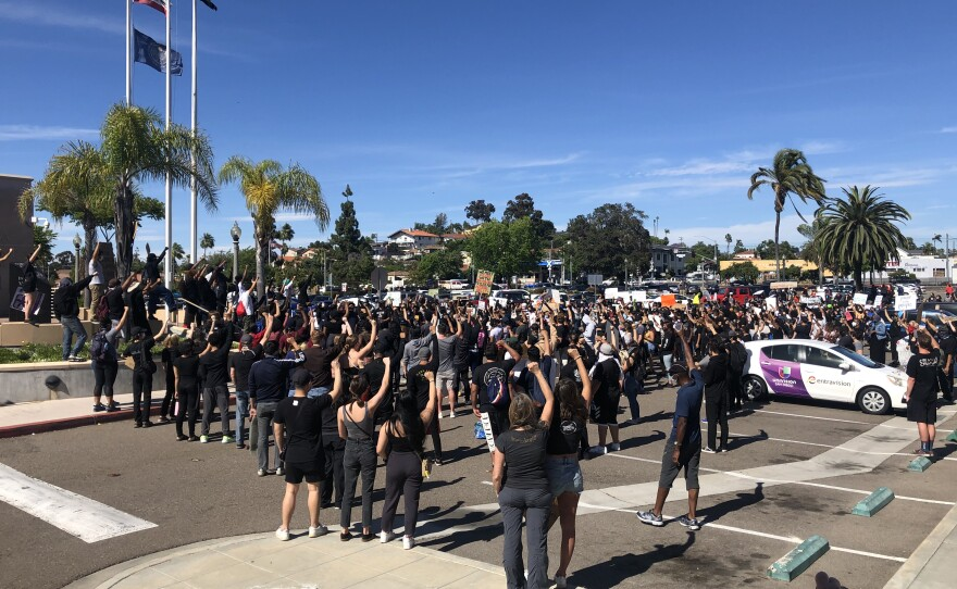 Protesters in La Mesa stand with their fists raised, May 30, 2020.