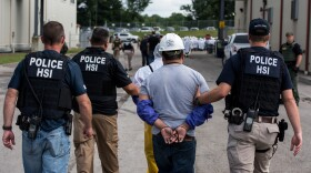 """""""We will not tolerate unscrupulous employers who exploit unauthorized workers,"""" Homeland Security Secretary Alejandro Mayorkas said, as he ordered a halt to mass workplace raids. Here, special agents with Homeland Security Investigations lead a worker away from a workplace raid in Ohio in 2018, part of a string of such operations during the Trump administration."""