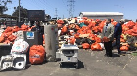 Caltrans officials stand in front of what they said is two weeks worth of collected trash, April 18, 2018.