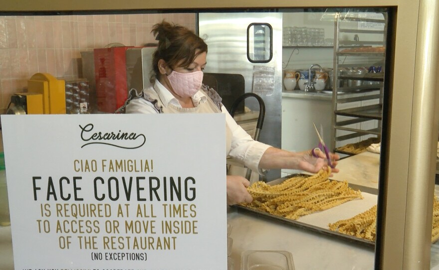 A worker making pasta at Cesarina in Point Loma with a sign requiring face covering on the premises, July 21, 2020.