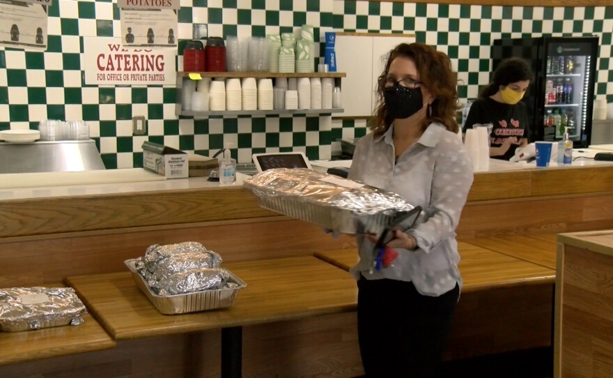 Encinitas resident Syndee Wood carrying a tray of burritos from Chicks Natural restaurant, Jan. 12, 2021.