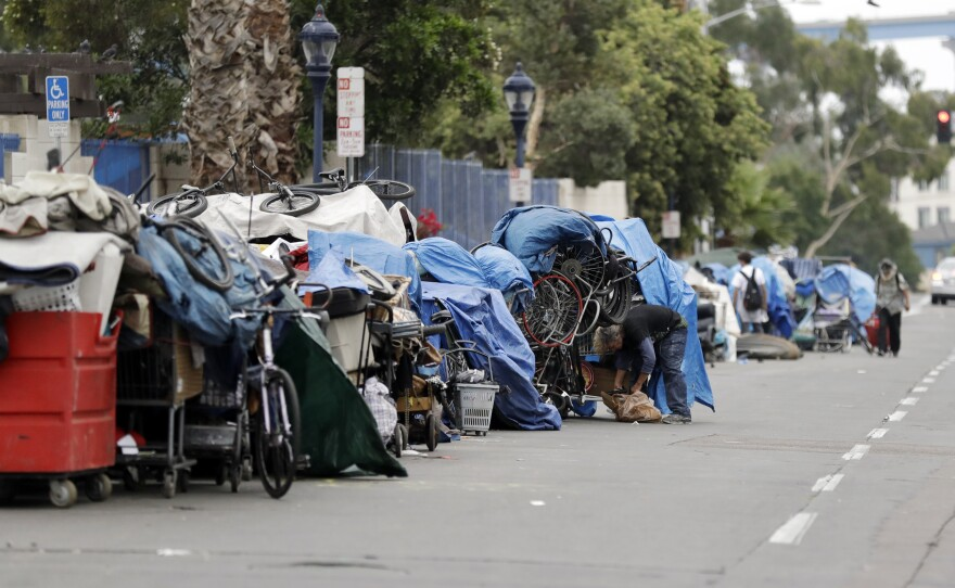 In this Sept. 19, 2017 photo, homeless people stand among their items along 17th Street in San Diego.
