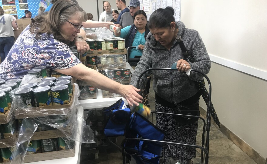 Volunteers with the Salvation Army hand people cans of food, produce, meat and rice during a Jacobs & Cushman San Diego Food Bank distribution event in El Cajon, May 15, 2019.