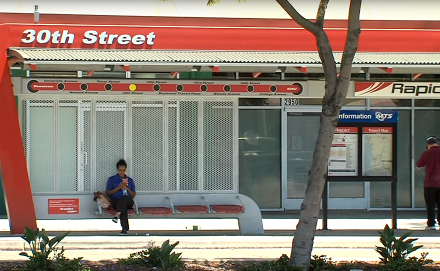 A woman sits at an MTS bus stop at 30th St. and El Cajon Blvd. in North Park, June 15, 2016.