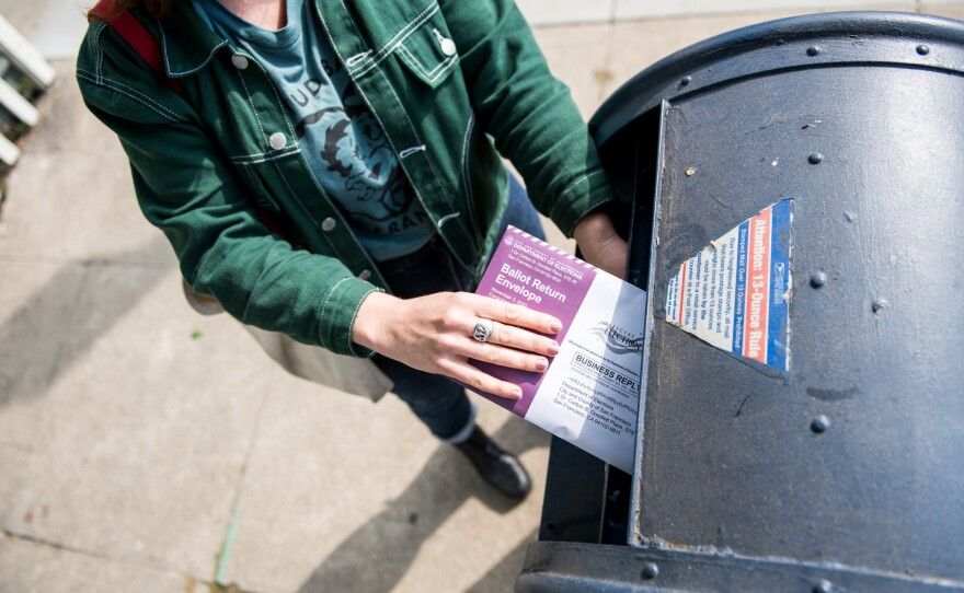 A San Francisco resident drops their mail-in ballot into a mailbox on Oct. 6, 2020.