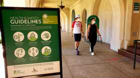 Pedestrians wearing face masks walk through Balboa Park. August 1, 2020.