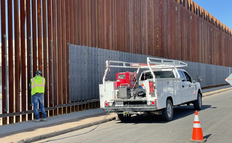 Worker is pictured welding sheets of metal onto the border wall in Calexico on May 5, 2021.