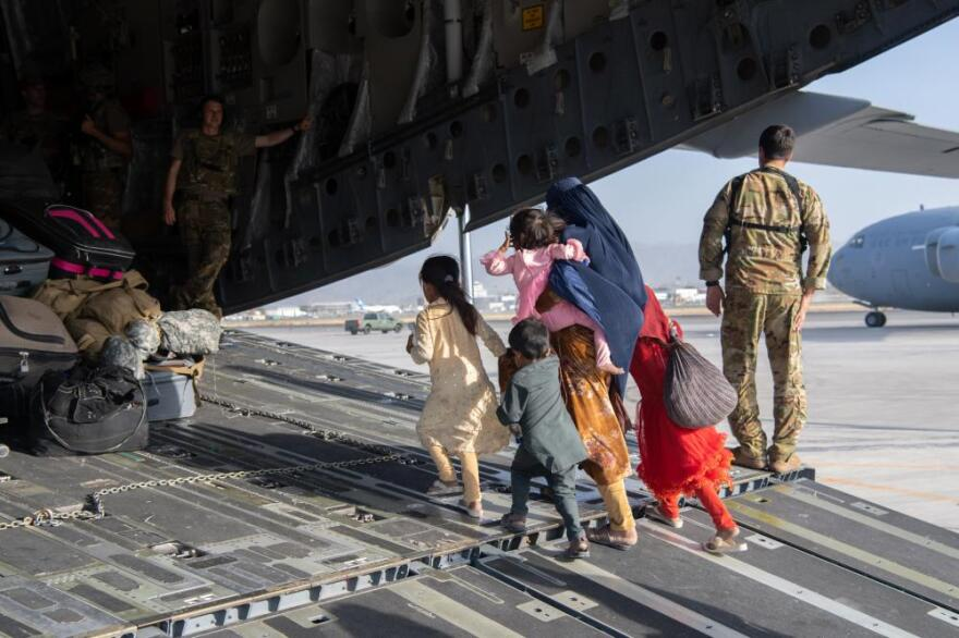 In this Aug. 24, 2021, file photo, provided by the U.S. Air Force, a family boarding a C-17 for their flight during ongoing evacuations at Hamid Karzai International Airport, in Kabul, Afghanistan.