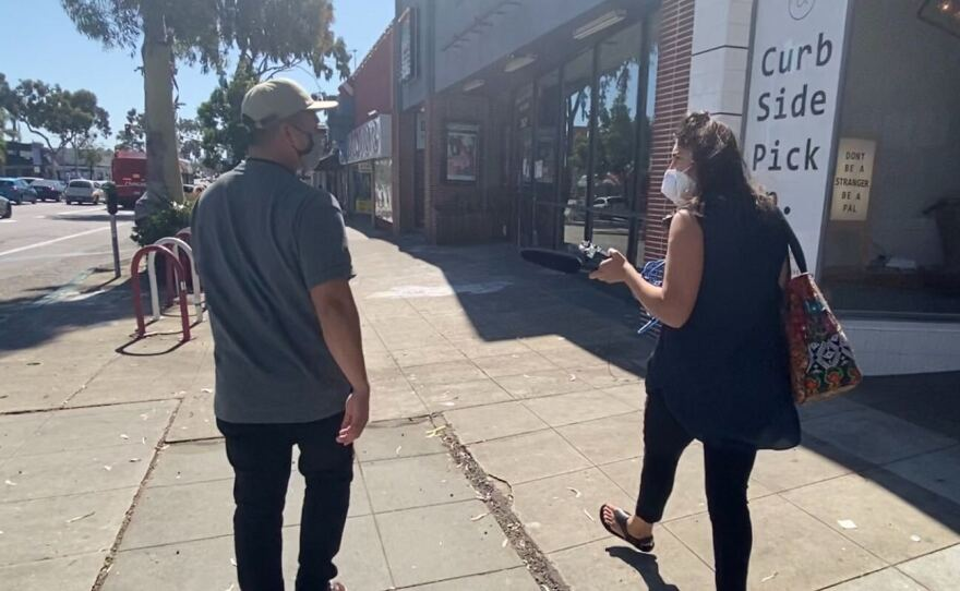 Jessie Angeles Jr. and KPBS reporter Shalina Chatlani walk through North Park as Angeles meets a number of his clients, who live on the street, May 28, 2020.