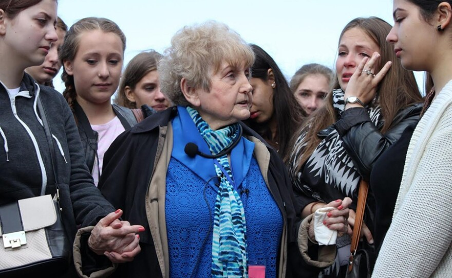 """Eva Kor (center) with German girls. """"EVA: A-7063"""" recounts the incredible true story of an Auschwitz survivor's journey to forgiveness and healing. After decades of torment and pain following her liberation, she decided to use her experiences as a teaching tool for other generations."""