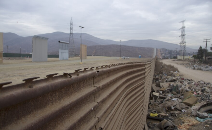 The prototypes for President Trump's wall are visible beyond the existing border fence, Jan. 8, 2017.