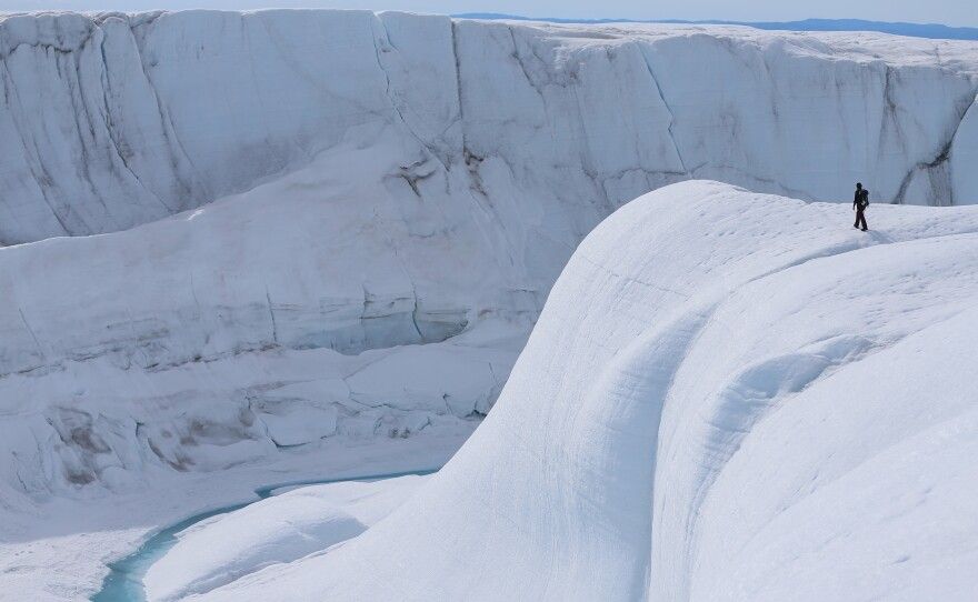 A researcher looks at a canyon created by a meltwater stream on the glacial ice sheet in Greenland in 2013.