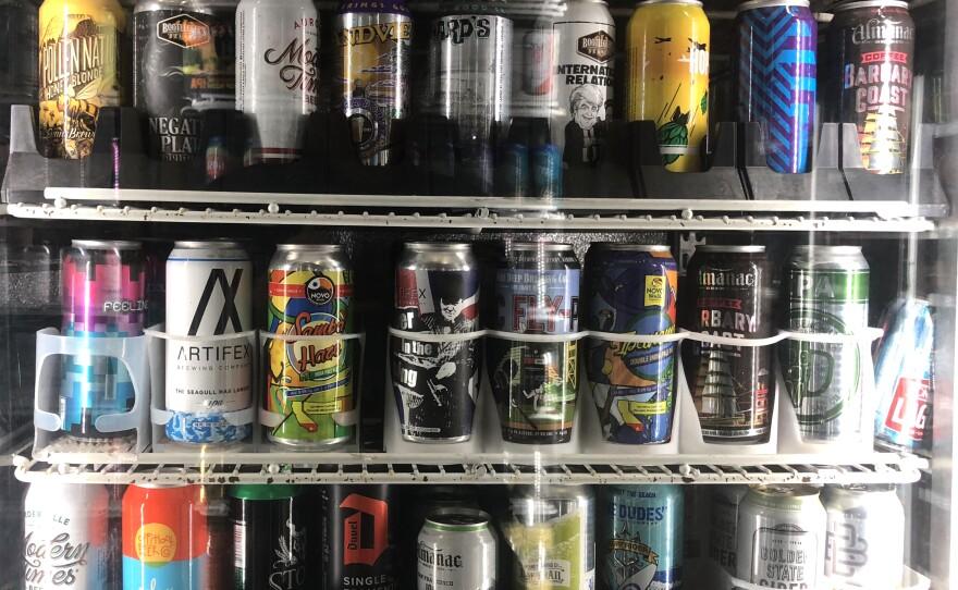 Beer cans sit on shelves inside of Keg N Bottle in San Diego, August 8, 2018.
