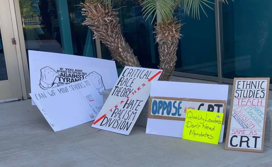 Signs protesting 'critical race theory' sit on the ground outside the Poway School District offices. September 9, 2021.