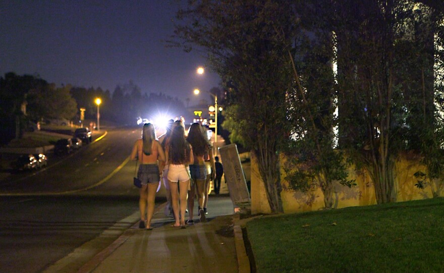 """Young women head to """"fraternity circle"""" close to the SDSU campus on a recent Saturday night."""
