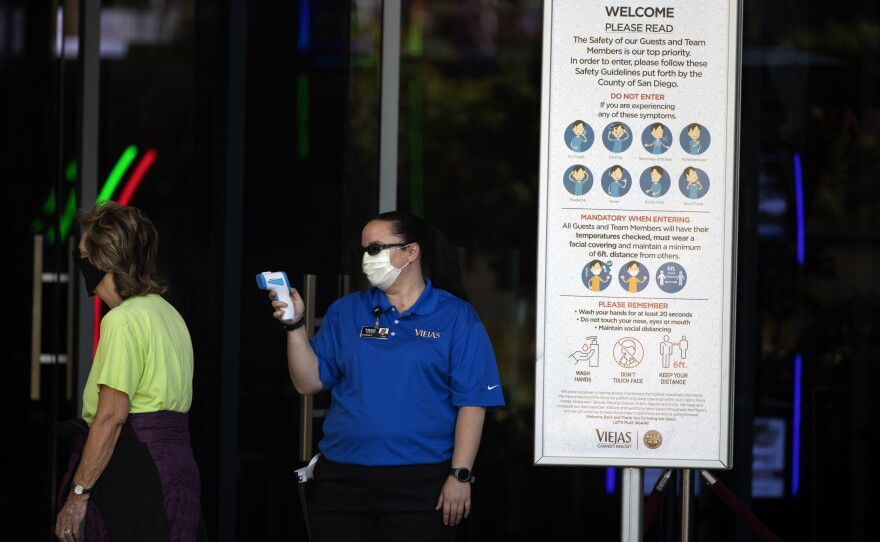 An official reads the temperature of a woman at the entrance to the Viejas Casino and Resort as it reopens Monday, May 18, 2020, in Alpine, Calif.