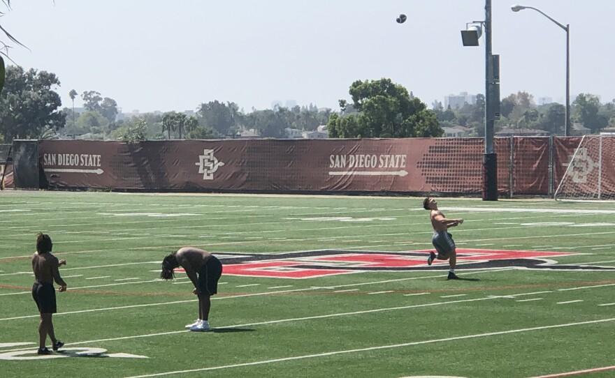 Three SDSU football players practice on a campus football field, Sept. 25, 2020.