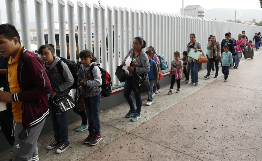People line up to cross into the United States to begin the process of applying for asylum near the San Ysidro Port of Entry in Tijuana, Mexico. President Trump has threatened to close the border to asylum-seekers.