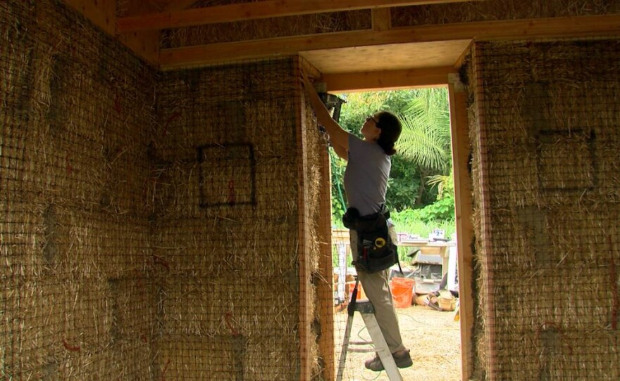 A worker does construction on a straw bale greenhouse in Encinitas, July 29, 2017.